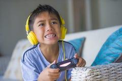 Aufgeregtes und glückliches spielendes Videospiel hispanischen Kleinkindes Oung online mit den Kopfhörern, die den Kontrolleur ge lizenzfreie stockbilder