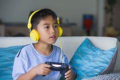 Aufgeregtes und glückliches spielendes Videospiel hispanischen Kleinkindes Oung online mit den Kopfhörern, die den Kontrolleur ge stockbilder