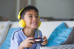 Aufgeregtes und glückliches spielendes Videospiel hispanischen Kleinkindes Oung online mit den Kopfhörern, die den Kontrolleur ge stockbild