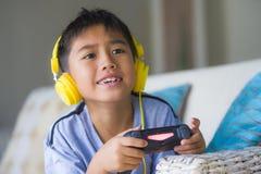 Aufgeregtes und glückliches spielendes Videospiel hispanischen Kleinkindes Oung online mit den Kopfhörern, die den Kontrolleur ge lizenzfreie stockfotos
