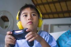 Aufgeregtes und glückliches spielendes Videospiel hispanischen Kleinkindes Oung online mit den Kopfhörern, die den Kontrolleur ge lizenzfreies stockbild