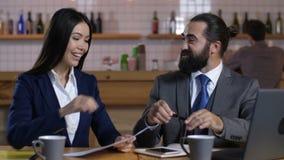 Aufgeregtes unterzeichnendes Abkommen des Hausbesitzers und des Grundstücksmaklers am Café stock video