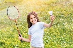 Aufgeregtes weibliches Kind, das Tennis auf Feld spielt Stockfotos