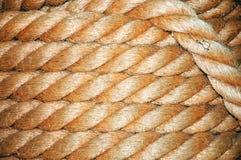 Aufgerollter Seilhintergrund der alten Marine Stockbild