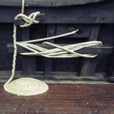 Aufgerolltes Seeseil auf hölzerner Plattform Stockbilder