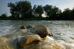 Aufgerundete Steine im Fluss Stockfotografie