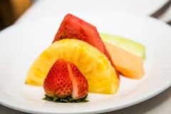 Aufgeteilte Erdbeere und geschnittene Ananas Stockbild