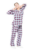 aufgewachtes Mädchen in den Pyjamas, die auf einen weißen Hintergrund ausdehnen stockfoto