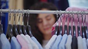 Aufhänger mit T-Shirts sind auf Gestell, Frau wählt Kleidung, unfocused Gesicht stock video