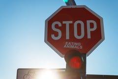 Aufkleber auf dem Verkehrsschild Halt, der einen Slogan des strengen Vegetariers bildet Stockbild