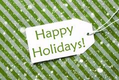 Aufkleber auf grünem Packpapier mit Schneeflocken, simsen frohe Feiertage Stockfotos