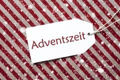 Aufkleber auf rotem Papier, Adventszeit bedeutet Advent Season, Schneeflocken Stockfotos