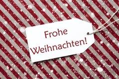 Aufkleber auf rotem Papier, Frohe Weihnachten bedeutet frohe Weihnachten, Schneeflocken Lizenzfreies Stockfoto