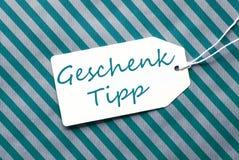 Aufkleber auf Türkis-Packpapier, Geschenk Tipp bedeutet Geschenk-Tipp Stockfotografie