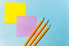 Aufkleber für das Notieren und die Bleistifte Bürothema auf blauem Hintergrund Stockbilder