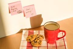 Aufkleber GUTER MORGEN, KAUFENDES AUTO auf dem Tisch zu Hause Hintergrund - Tischdecke mit Tasse Kaffee und Plätzchen Lizenzfreie Stockbilder