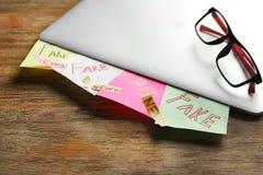 Aufkleber mit den Wörtern GEFÄLSCHT und den NACHRICHTEN unter Laptop auf Holztisch stockbild