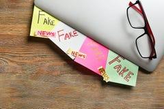 Aufkleber mit den Wörtern GEFÄLSCHT und den NACHRICHTEN unter Laptop auf Holztisch stockfoto