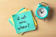 Aufkleber mit Phrase wenn nicht jetzt, wann? und Wecker auf Tabelle Schmutz-Hintergrund f?r Ihre Ver?ffentlichungen stockfoto