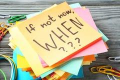 Aufkleberpapiere mit inspirierend Phrase wenn nicht jetzt, WENN??? auf Holztisch stockfotografie