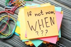 Aufkleberpapiere mit inspirierend Phrase wenn nicht jetzt, WENN??? auf Holztisch lizenzfreie stockbilder
