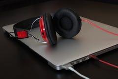 Aufladungsnotizbuch mit verbundenen roten Kopfhörern Lizenzfreie Stockfotografie