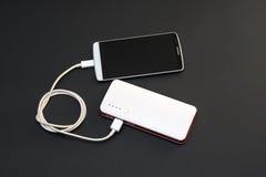 Aufladungssmartphone Powerbank auf dunklem Hintergrund Stockfoto