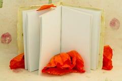 Auflage des Papiers mit leerer Seite und Mohnblume Stockfotografie