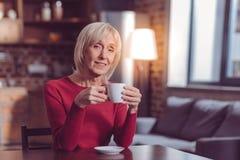 Aufmerksame ältere Frau, die auf Kamera lächelt lizenzfreies stockfoto