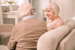 Aufmerksame blonde reife Frau, die auf ihren Partner hört stockfotografie