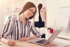 Aufmerksame Damenschneiderin, die einen Laptop verwendet lizenzfreie stockfotos