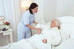 Aufmerksame Krankenschwester, die ältere Dame tröstet stockfotografie