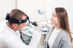 Aufmerksame medizinische Arbeitskraft des Facharztes für Hals- und Ohrenleiden sehr, die Nase seines Besuchers betrachtet Lizenzfreies Stockbild