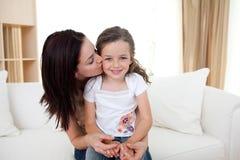 Aufmerksame Mutter, die ihr kleines Mädchen küßt Stockbild