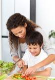 Aufmerksame Mutter, die ihrem Sohn hilft, Gemüse zu schneiden Stockbilder