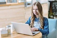 Aufmerksame weibliche Person, die mit Computer arbeitet Stockbild