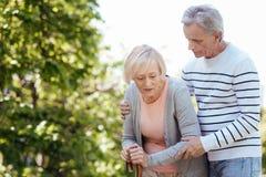 Aufmerksamer Alternmann, der draußen ältere Frau stützt Lizenzfreie Stockfotos