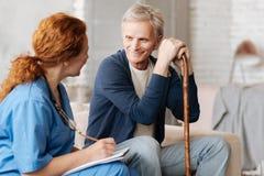 Aufmerksamer empfindlicher Therapeut, der mit ihrem älteren Patienten spricht Stockfoto