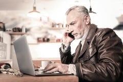 Aufmerksamer Geschäftsmann, der pro Telefon im Café spricht stockfoto