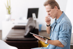 Aufmerksamer Mann, der mit Tablette arbeitet Lizenzfreie Stockfotos