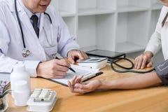 Aufmerksamer Patient Professordoktors, der messend überprüfend ist und Blutdruck zum Patienten-, Krankenhaus- und Medizinkonzept stockbilder