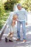 Aufmerksamer Pensionär, welche draußen älterer Frau hilft Lizenzfreie Stockbilder