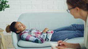 Aufmerksamer Psychologe hält Beratung mit Afroamerikanerfrau, hört und macht Anmerkungen, während Kunde ist stock video footage