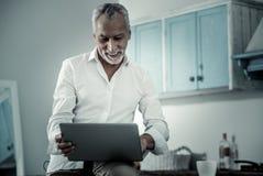 Aufmerksamer reifer Mann, der mit Computer arbeitet stockfotografie