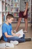 Aufmerksames Schülerlesebuch in der Bibliothek Lizenzfreie Stockfotografie