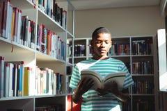 Aufmerksames Schülerlesebuch in der Bibliothek Stockbilder