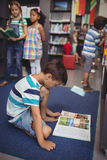 Aufmerksames Schülerlesebuch in der Bibliothek Lizenzfreie Stockbilder