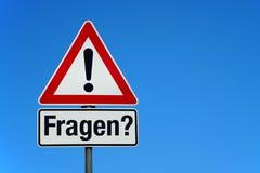 Aufmerksamkeit und Warnzeichen mit deutschem Text FRAGEN - Übersetzung: Fragen lizenzfreies stockfoto