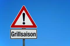 Aufmerksamkeit und Warnzeichen mit deutschem Text GRILLSAISON - Übersetzung: Grilljahreszeit stockfotografie