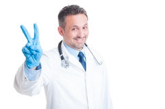 Aufmunternder Doktor oder Mediziner, die Frieden und Sieg zeigen, gestikulieren Stockfotografie